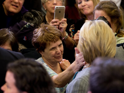 A woman touches the cheek of Democratic presidential candidate Hillary Clinton at a rally in Des Moines, Iowa.