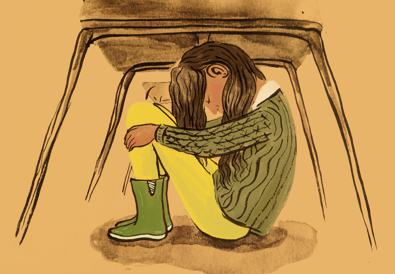 Student hiding under a desk