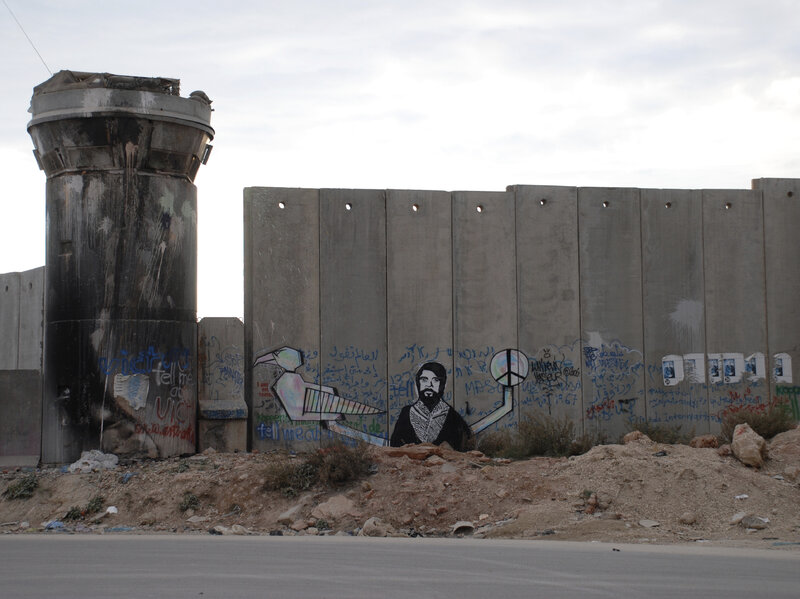 The Israeli-built separation wall at Qalandia checkpoint, between the cities of Ramallah and Jerusalem. The watch tower shows signs of being vandalized with paint and fire.