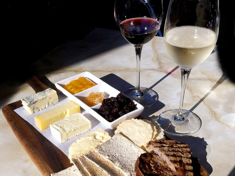 Red and white wine in glasses with a cheese platter of a variety of cheeses with crackers and bread