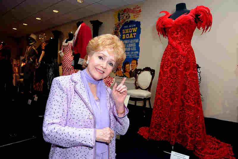 "Debbie Reynolds poses alongside one of the original costumes she wore in the The Unsinkable Molly Brown, on display at The Paley Center For Media's Reception For ""Debbie Reynolds: The Exhibit"" in August 2011 in Beverly Hills, Calif."