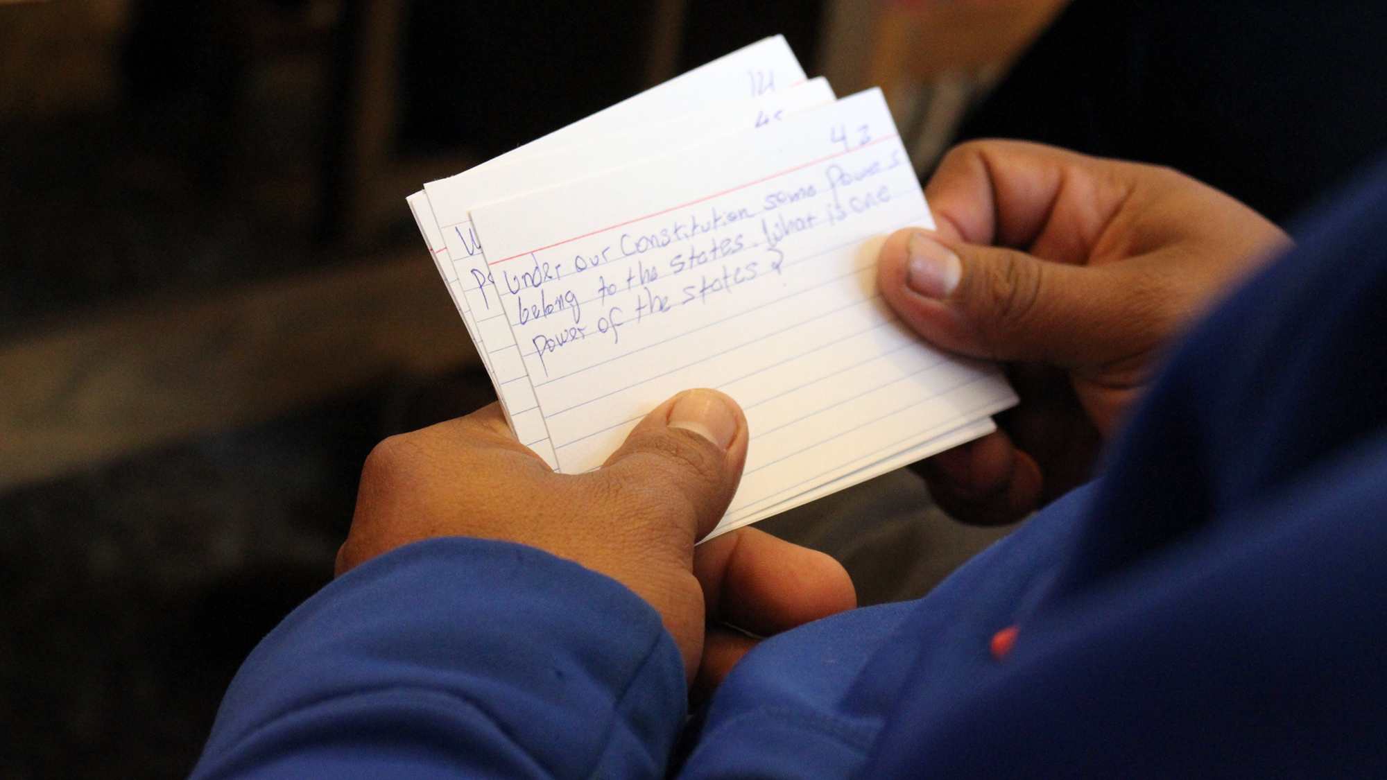 A student practices with flashcards with facts about American government during a class at the public library in Brush, Colo.