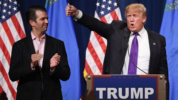 Donald Trump Jr. looks on as his father, then-GOP presidential candidate Donald Trump, waves after speaking at a caucus night watch party at the Treasure Island Hotel & Casino in Las Vegas, Nev., in February 2016.