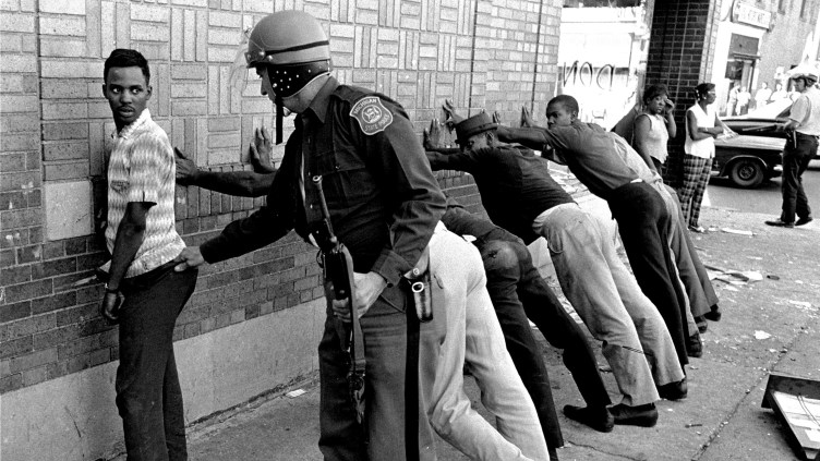 In this photo from July 24, 1967, a police officer searches a youth on Detroit