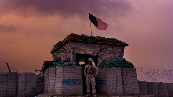 A U.S. Marine from the 1st Battalion, 8th Marines, Alpha Company looks out as an evening storm gathers above an outpost near Kunjak, in southern Afghanistan
