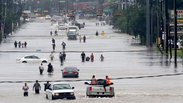 People walk through the flooded waters of Telephone Rd. in Houston as the fourth largest city in the U.S. battles Tropical Storm Harvey and resulting floods.