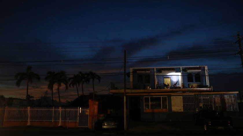 A man rests in a hammock, using a battery-operated light, in an area without electricity more than two weeks after Hurricane Maria hit the island in San Isidro, Puerto Rico.