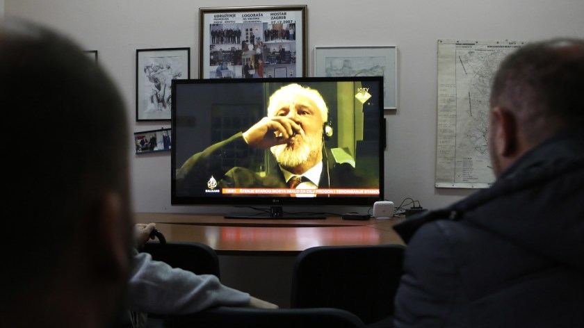 """Bosnian viewers watch as Slobodan Praljak brings a small glass of liquid to his lips at the International Criminal Tribunal for the former Yugoslavia on Wednesday. Praljak, who had just had his 20-year sentence for war crimes upheld, ingested the liquid and declared """"I have just drunk poison."""" He died just hours later."""