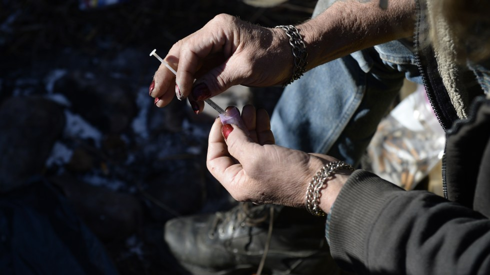 A homeless man in Denver draws heroin into a syringe. Treatment centers in the city say patterns of drug use seem to be changing. While most users once relied on a single drug — typically painkillers or heroin or cocaine — an increasing number now also use meth.