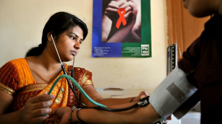 A nurse tests an HIV-positive patient at a clinic in Bangalore, India.