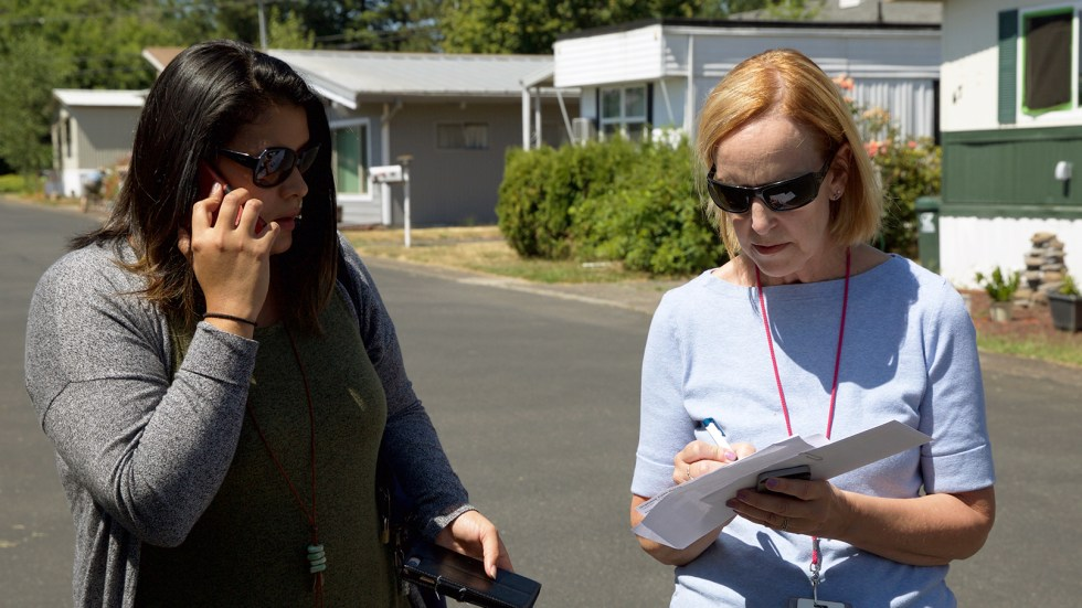 Mary Horman (left), a registered nurse for Clackamas County, and Liz Baca, a disease intervention specialist for the county, search for the right address in an Oregon neighborhood. Part of their job is to get information to people who may have a serious, treatable infection, yet not realize it.
