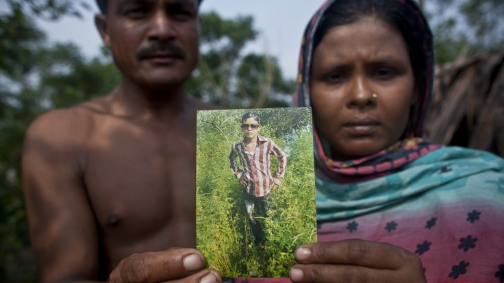 Kamal Hosen and Rahima Khartoum, Rohingya refugees in Bangladesh, hold a photograph of their 14-year-old son, Din Mohammad. A victim of human trafficking, he was eventually rescued from a camp in Thailand.