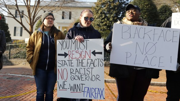 Demonstrators hold signs and chant in Richmond, Va., on Feb. 2, 2019. They were calling for the resignation of Gov. Ralph Northam after a racist photo on his medical school yearbook page came to light. He denies that he is in the photo but admits to once dressing in blackface.