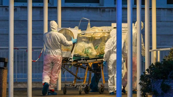 Medical workers stretch a patient into a newly built temporary hospital on March 16 in Rome. Doctors in Italy are making difficult decisions on who should receive care.