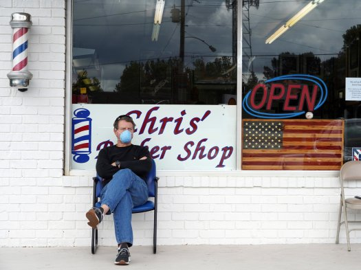 Dan Settle sits outside Chris' Barber Shop as he waits his turn for a haircut in Lilburn, Georgia on April 24, 2020. - Georgia Governor Brian Kemp eased restrictions allowing some businesses such as barber shops to reopen to get Georgia's economy going during the coronavirus pandemic. (Photo by Tami Chappell / AFP) (Photo by TAMI CHAPPELL/AFP via Getty Images)
