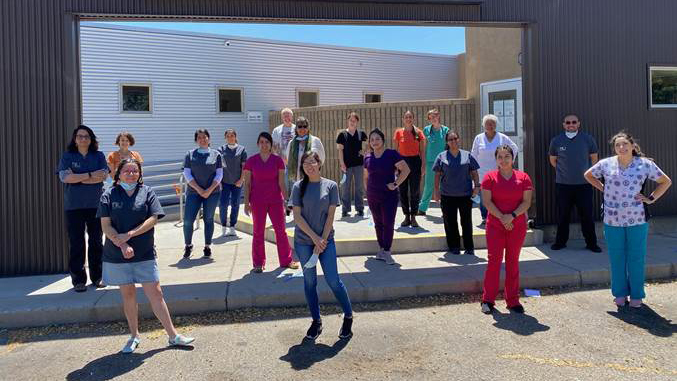 Casa de Salud clinicians, staff and health apprentices socially distance outside their New Mexico clinic. The facility is one of many social safety net clinics that haven