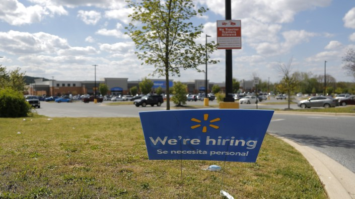 A Walmart store in Maryland advertises its hiring during the coronavirus pandemic. The big retailer says it hired 235,000 new staffers to keep up with demand.