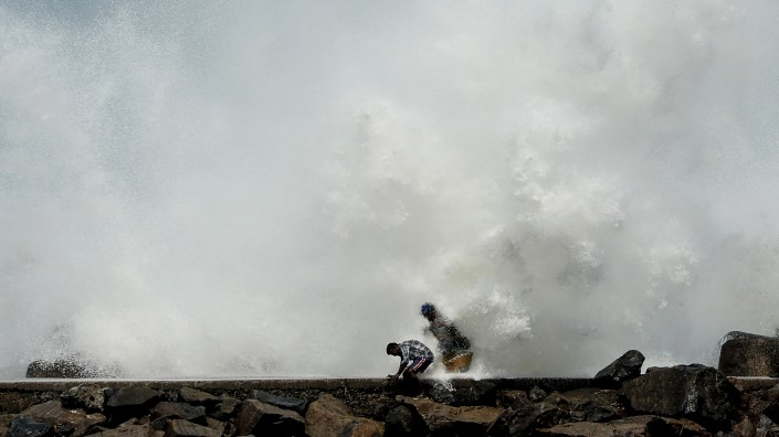 Two men duck for cover as waves generated by Cyclone Amphan smash against a breakwater Tuesday in Chennai, India. Farther north along India