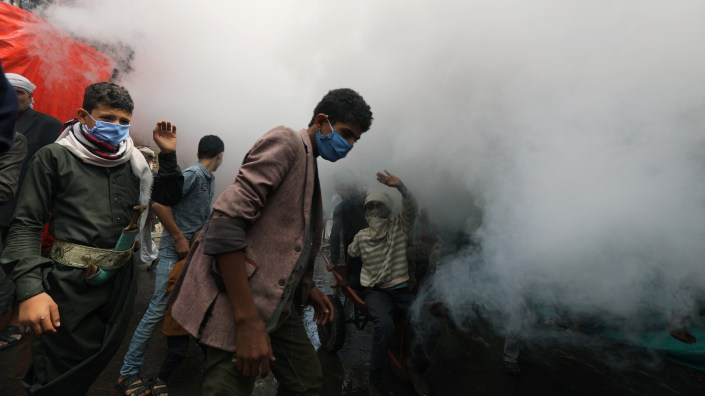 People wear face masks as health workers fumigate a market amid concerns about the spread of COVID-19 in Sanaa, Yemen.