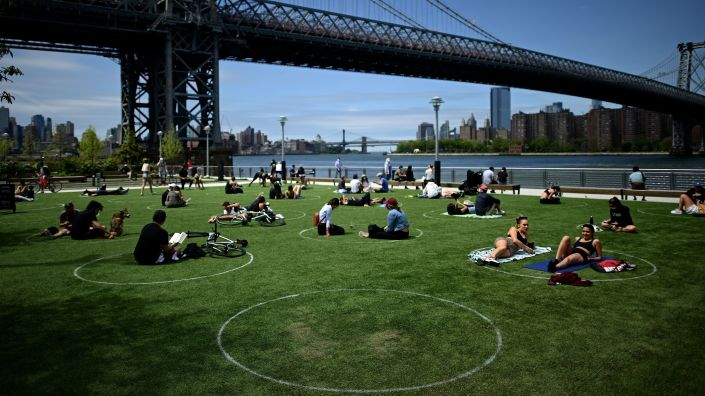 People relax in the sun while practicing social distancing last weekend in New York City