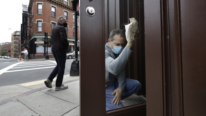 Manager Mike Bonavita wears a protective mask as he cleans windows at the Quattro Italian restaurant in Boston on May 12 during the coronavirus pandemic. This month, Massachusetts