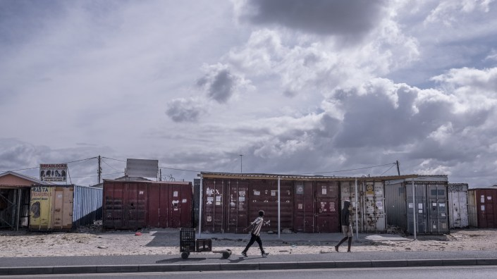 Boys walk past shuttered businesses in the township of Khayelitsha, Cape Town, South Africa, during the country