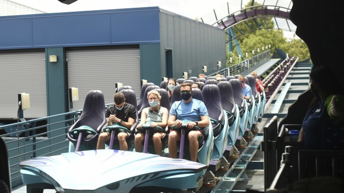 Visitors wear face masks while riding a roller coaster at the SeaWorld amusement park in Orlando, Fla., on Thursday.  SeaWorld is reopening its parks this week, after being closed for months due to the COVID-19 pandemic. Florida and more than 20 other states continue to see a rise in new daily cases.