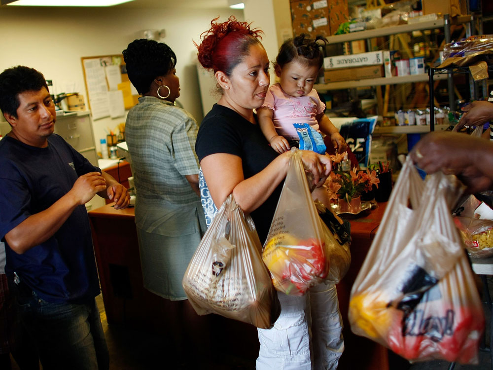 Abran Lopez and Angelina Martinez receive groceries from a food co-op in Fort Lauderdale, Fla.
