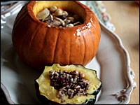 Baked pumpkin and stuffed squash sit on a white platter