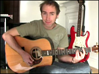 Justin Sandercoe plays a B minor bar chord in a video teaching how to play a Coldplay song.
