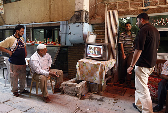 Iraqi men in Baghdad watch a live broadcast on satellite TV of President Obama's speech in Cairo