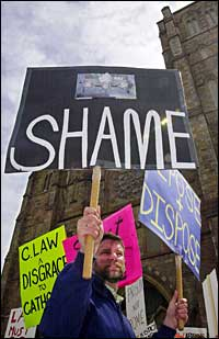Protesters gather outside the Cathedral of the Holy Cross in Boston, demanding the resignation of C