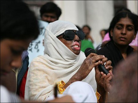Haseena Hussain holds microphone, wearing dark glasses and covered by shawl