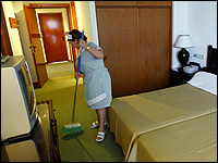A maid cleans a hotel room.