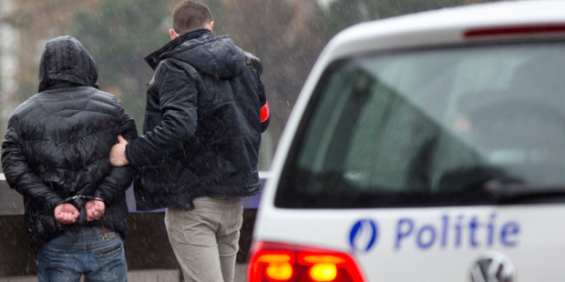 Police detain a man in handcuffs after stopping and searching his car which had French number plates in Brussels. Photo / AP