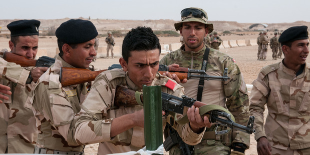 A Danish trainer tells an Iraqi army trainee to correct his weapon's position during a simulated exercise. Photo / US Army