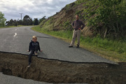Ten-year-old Jack Satterthwite sits on the lip of a large crack in the road in Waiau caused by the magnitude 7.8 quake that struck North Canterbury a week ago. Photo / File