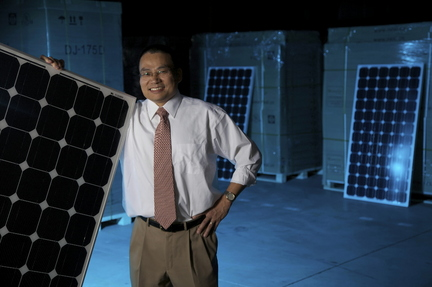 Thomas Boyd/The Oregonian Centron President Ocean Yuan stands next to one of the companys solar panels at Centrons Eugene warehouse.