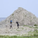 Children walking past some of the heaps of sand gathered about 4 years ago for filling of part of the seashore in Ayetoro but have not been used since then