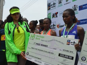 Mrs Iara Oshiomhole, Edo State First Lady presents a dummy cheque to Tanui Nkele of Kenya, winner of the 1st prize with 33.34 minutes in the 3rd edition of the Annual IAAF certified 10km Okpekpe race, on Saturday.