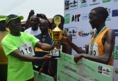 Governor Adams Oshiomhole of Edo State presents a trophy to Alex Korio of Kenya, winner in the male Category of the 10km Okpekpe race with a time of 29,20 minutes at the 3rd edition of the Annual IAAF certified 10km Okpekpe race, on Saturday.
