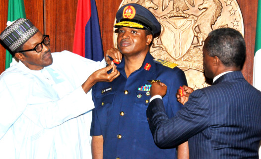 President Muhammadu Buhari (L)  Aided By Vice-President Yemi Osinbajo  In Decorating The Chief Of Air  Staff,  Air Vice-Marshal Sadique Abubarkar  With His New Rank Of  Air-Marshal  At The Presidential Villa In Abuja On Thursday (13/8/15) | NAN