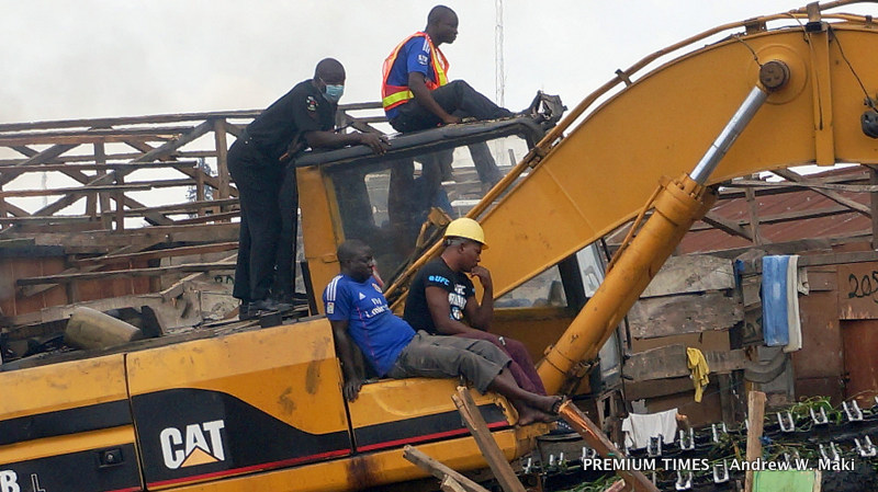 Nigerian Police Force officer rides on excavator on morning of 19 Sept 2015