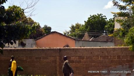 Joseph Jidda walking beside the destroyed residence of the Parish priest of St.Pius De 10th Catholic Church
