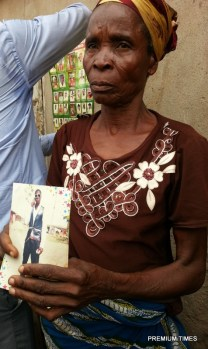 An old woman displaying the photo of her son that was killed in Omoku