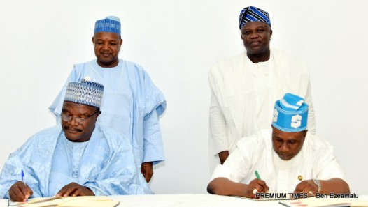 Lagos State Commissioner for Agriculture, Mr. Oluwatoyin Suarau (right), with Permanent Secretary, Kebbi State Ministry of Agriculture, Dr. Nababa Adamu (left), signing a Memorandum of Understanding on the Development of Commodity Value Chains between the two States while Lagos State Governor, Mr. Akinwunmi Ambode (right behind) and Kebbi State Governor, Alhaji Atiku Bagudu (left behind) watch, at the Lagos House, Ikeja, on Wednesday, March 23, 2016.