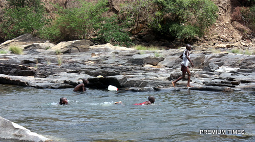 Some children swimming in the pool of the waterfall