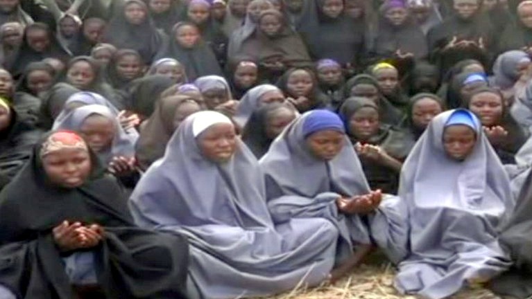 FILE PHOTO: A screengrab taken on May 12, 2014, from a video of Nigerian Islamist extremist group Boko Haram obtained by AFP shows girls, wearing the full-length hijab and praying in an undisclosed rural location. Boko Haram released a new video on claiming to show the missing Nigerian schoolgirls, alleging they had converted to Islam and would not be released until all militant prisoners were freed. A total of 276 girls were abducted on April 14 from the northeastern town of Chibok, in Borno state, which has a sizeable Christian community. Some 223 are still missing. AFP PHOTO / BOKO HARAM