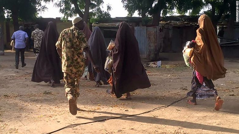Chibok girls being accompanied by soldiers after their release   Photo Credit: CNN