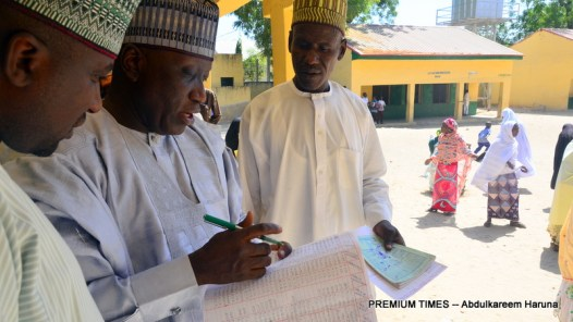 Borno's Head of Service, Barrister Yakubu Bukar marking register of teachers at Lamisula Primary and Junior Secondary School in Maiduguri.